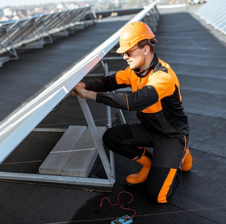 pracownik montujący panele